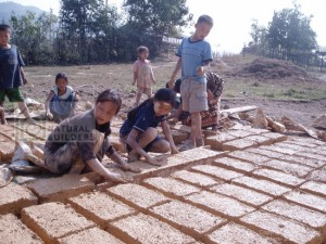 Youth creating adobe earthen blocks for their community center. Our team facilitated the design, funding and build of the project. 2003 Phoudindaeng village, Laos